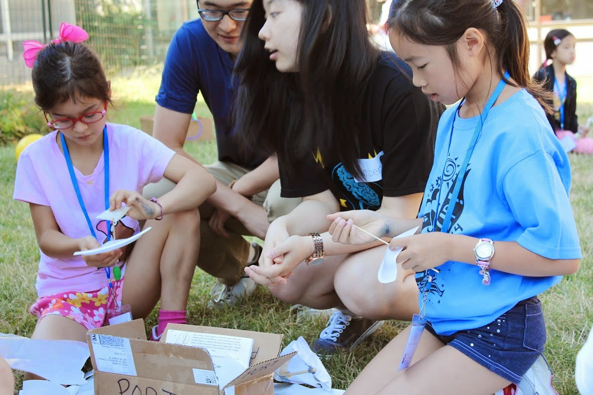 Two girls building boats with summer camp instructors